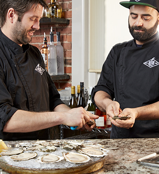 Two men shucking oysters at an oyster bar